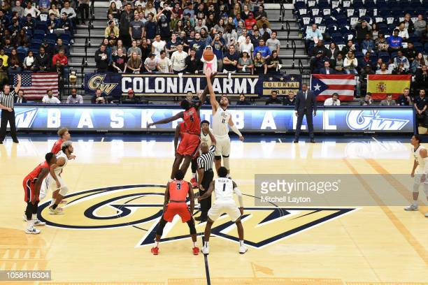 Arnaldo Toro of the George Washington Colonials tips off the ball over Jeff Otchere of the Stony Brook Seawolves during a college basketball game at...