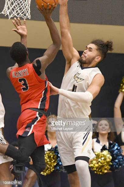 Arnaldo Toro of the George Washington Colonials tires to block shot of Elijah Olaniyi of the Stony Brook Seawolves during a college basketball game...