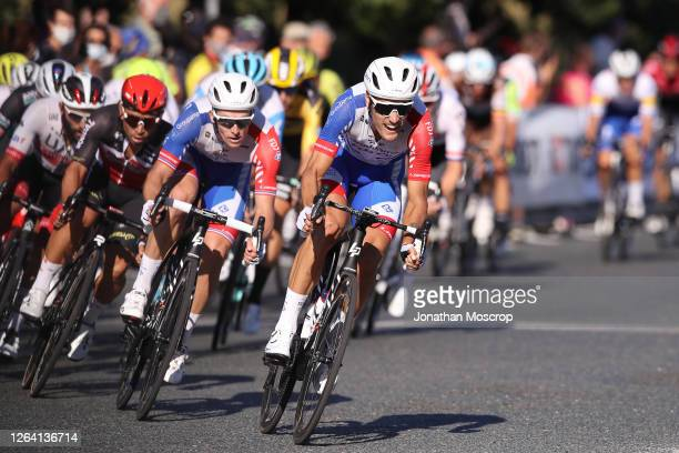Arnaud Demare of Groupama-FDJ is lead by team mate Jacopo Guarnieri into the final corner ahead of the home straight before being crowned champion of...