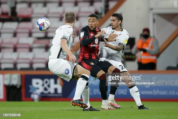 Arnaut Danjuma of Bournemouth is closed down by Ryan Bennett and Kyle Naughton of Swansea City during the Sky Bet Championship match between AFC...