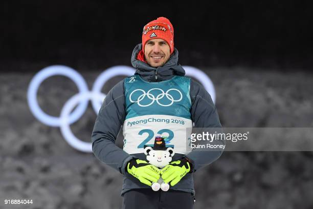 Arnd Peiffer of Germany celebrates winning the gold medal during the victory ceremony after the Men's 10km Sprint Biathlon on day two of the...