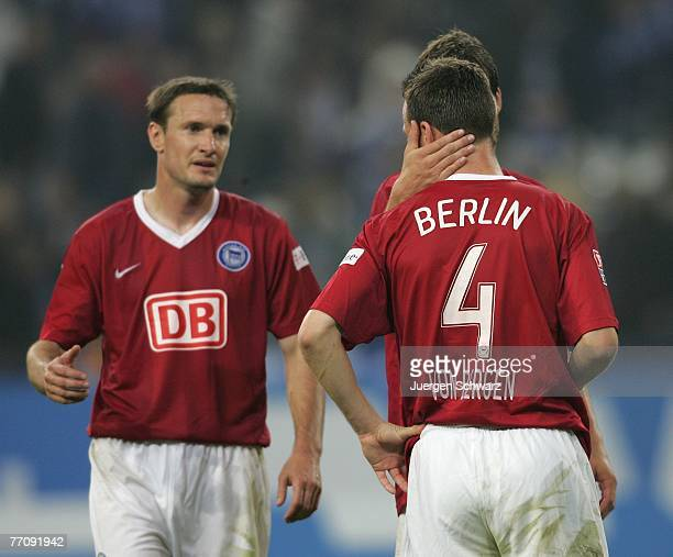 Arne Friedrich of Berlin hugs his teammate Steve von Bergen after they lost the Bundesliga match between FC Schalke 04 and Hertha BSC Berlin at the...