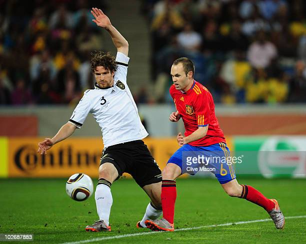 Arne Friedrich of Germany attempts to tackle Andres Iniesta of Spain during the 2010 FIFA World Cup South Africa Semi Final match between Germany and...