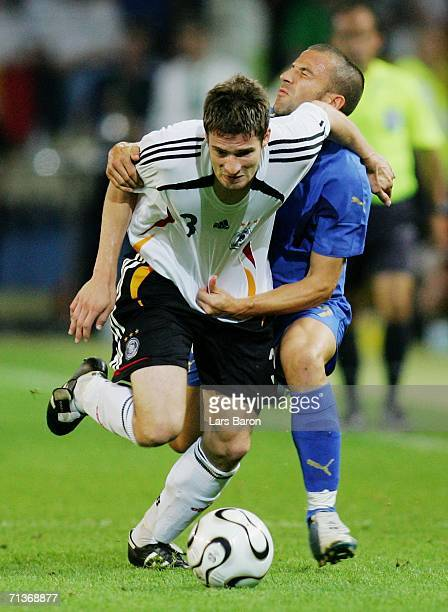 Arne Friedrich of Germany tangles with Alessandro Del Piero of Italy during the FIFA World Cup Germany 2006 Semifinal match between Germany and Italy...