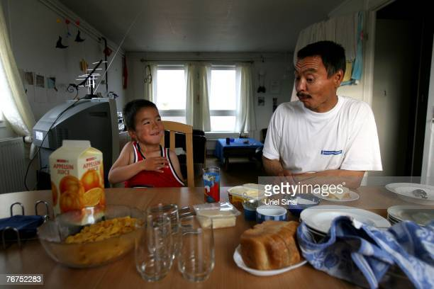 Arne Lange a 39yearold Inuit fisherman eats breakfast with his fiveyearold son Angut Rosbach August 27 2007 in the village of Ilimanaq Greenland...