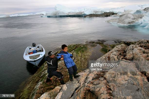 Arne Lange a 39yearold Inuit fisherman lifts his fiveyearold son Angut Rosbach on an island as they arrive there to hunt seals August 26 2007 near...