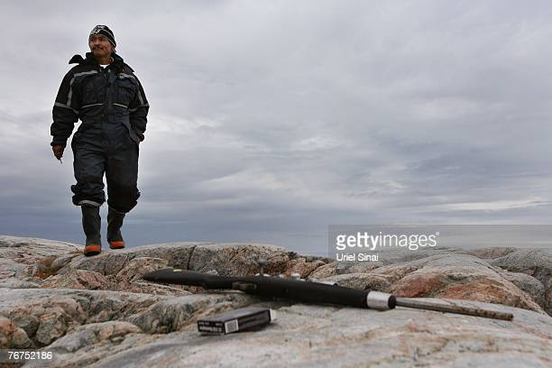 Arne Lange a 39yearold Inuit fisherman walks towards his rifle as he hunts seals from an island August 26 2007 near his home village of Ilimanaq...