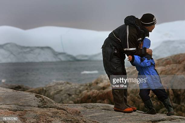 Arne Lange a 39yearold Inuit fisherman warms his fiveyearold son Angut Rosbach on an island where they came to hunt seals August 26 2007 near their...