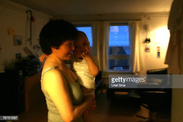 Arne Lange's wife Martha Rosbach holds their oneyearold son Syren in their home August 26 2007 in Ilimanaq Greenland Lange who has largely given up...