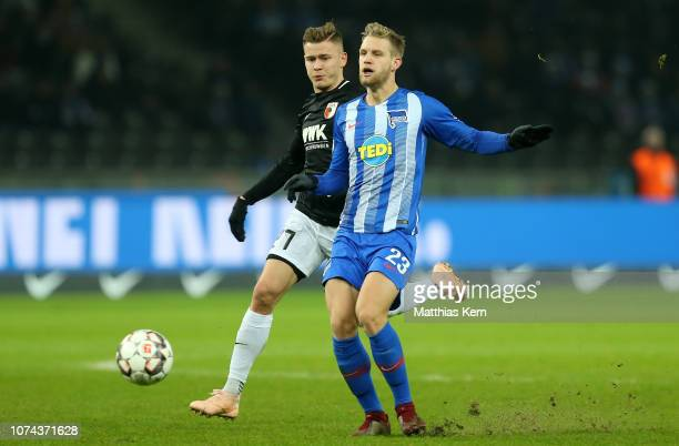 Arne Maier of Berlin challenges for the ball with Alfred Finnbogason of Augsburg during the Bundesliga match between Hertha BSC and FC Augsburg at...