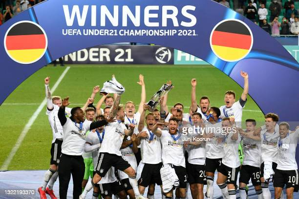 Arne Maier of Germany lifts the UEFA European Under-21 Championship trophy as their team mates celebrate following victory in the 2021 UEFA European...