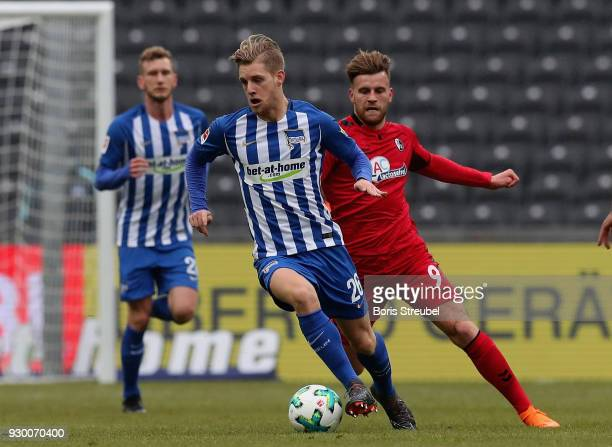Arne Maier of Hertha BSC is challenged by Lucas Hoeler of SC Freiburg during the Bundesliga match between Hertha BSC and SportClub Freiburg at...