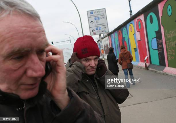 Arno Paulus a local real estate development opponent and Thierry Noir the artist who painted the murals visible behind make phone calls while...