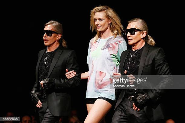 Arnold and Oskar Wess with model Anastassija Makarenko walk down the runway during GarconF fashion show at BalloniHallen on August 5 2014 in Cologne...