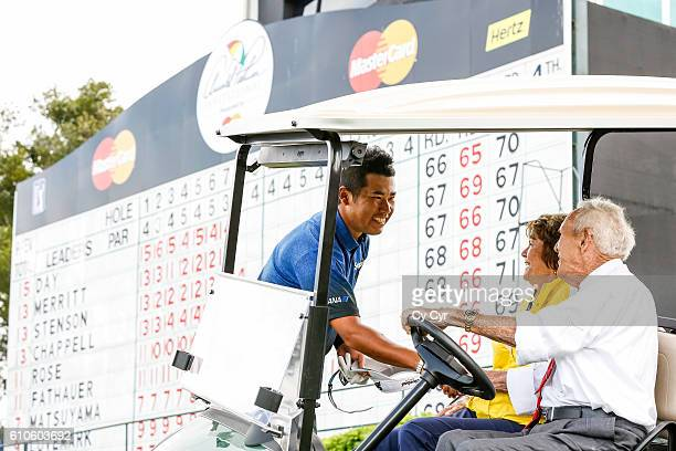 Arnold Palmer and his wife Kathleen 'Kit' Palmer greet Hideki Matsuyama of Japan on the 16th hole during the final round of the Arnold Palmer...