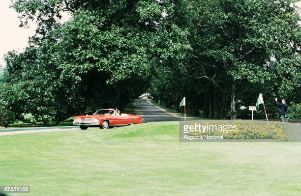 Arnold Palmer drives up Magnolia Lane in his red Cadillac during the 1973 Masters Tournament at Augusta National Golf Club in April 1973 in Augusta...