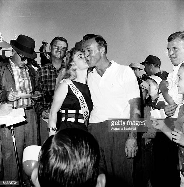 """Arnold Palmer gets a kiss on the cheek from """"Miss Golf 1958"""" during the 1958 Masters Tournament at Augusta National Golf Club in April 1958 in..."""