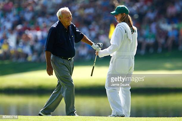 Arnold Palmer hands a club to caddie Kelly Tilghman during the Par 3 Contest on the third day of practice prior to the start of the 2008 Masters...