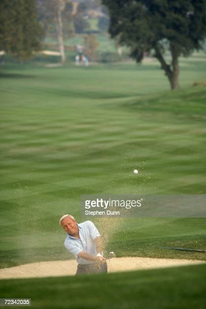 Arnold Palmer hits a shot out of the bunker, which he holed for an eagle, during the 1990 RMCC Invitational at the Sherwood Country Club in Thousand...