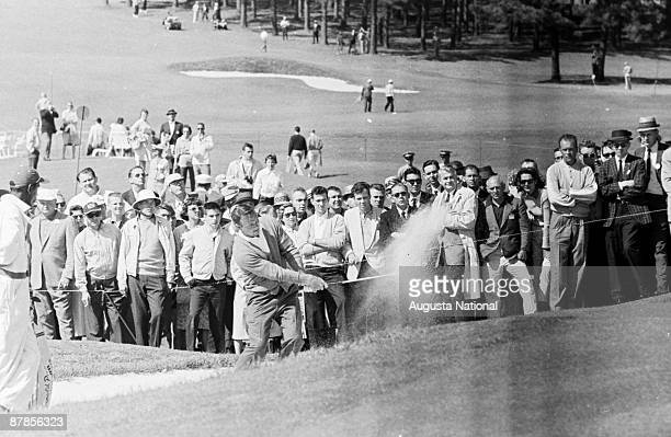 Arnold Palmer hits out of a bunker on the ninth hole during the 1961 Masters Tournament at Augusta National Golf Club in April 1961 in Augusta Georgia