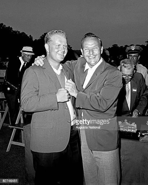 Arnold Palmer laughs with Jack Nicklaus while adjusting Nicklaus' second green jacket during the Presentation Cereomy of the 1965 Masters Tournament...