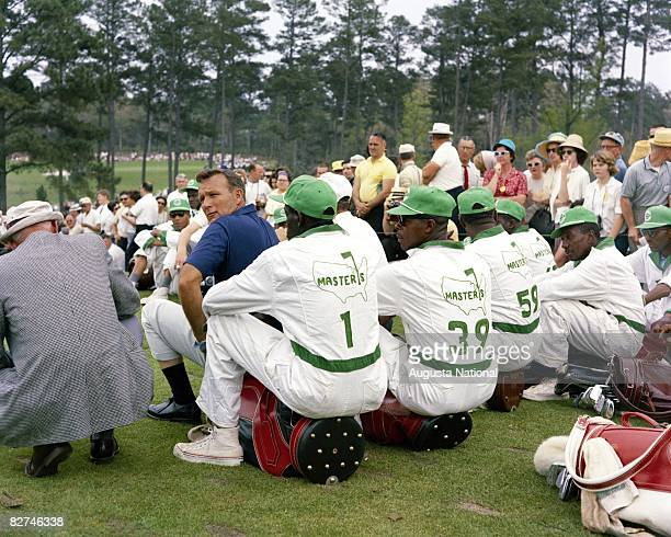 Arnold Palmer looks over his shoulder as he sits with a group of caddies during the 1965 Masters Tournament at Augusta National Golf Club on April...