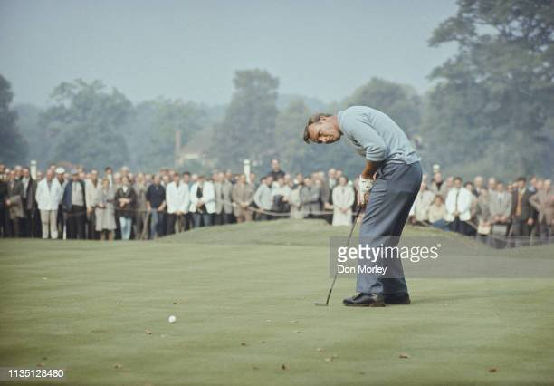 Arnold Palmer of the United States follows the ball to the hole as the spectators look on during the first Piccadilly World Match Play Championship...
