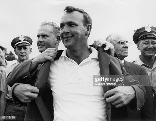 Arnold Palmer puts on the Green Jacket with the help of Jack Nicklaus with Chairman Clifford Roberts in the background at The Presentation Ceremony...