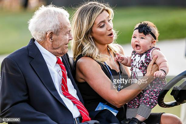 Arnold Palmer sits with Ellie Day wife of Jason Day of Australia and their daughter Lucy Day following Jason's trophy ceremony on the 18th hole green...