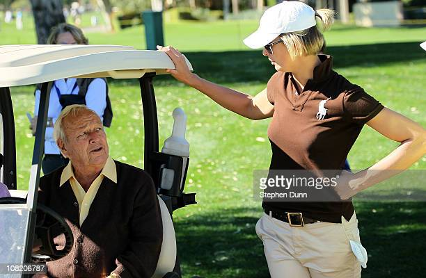 Arnold Palmer talks with Angie Watson wife of PGA Tour golfer Bubba Watson on the 16th hole during round two of the Bob Hope Classic at the La Quinta...