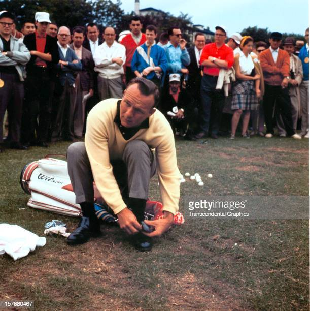 Arnold Palmer ties his shoes before a demonstration for the fans at a tournament circa 1955 in an unknown American location