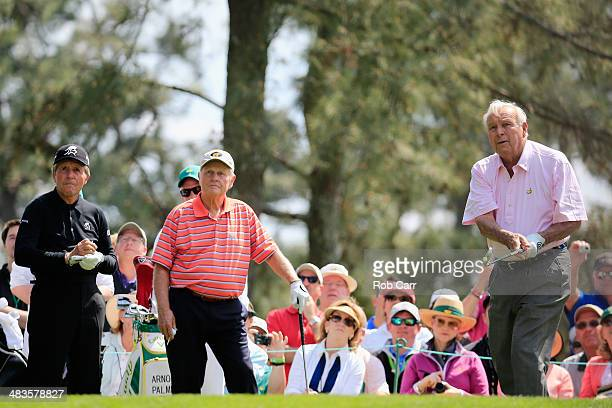 Arnold Palmer watches his tee shot on the opening hole as Jack Nicklaus and Gary Player look on during the 2014 Par 3 Contest prior to the start of...