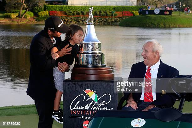 Arnold Palmer watches Jason Day of Australia as he holds his son Dash while kissing the trophy following the final round of the Arnold Palmer...