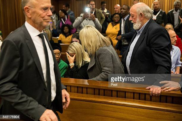 Arnold Pistorius , uncle of Oscar Pistorius, walks in front of the stand where Reeva Steenkamp's cousin Kim Martins cries and is comforted by Reeva's...
