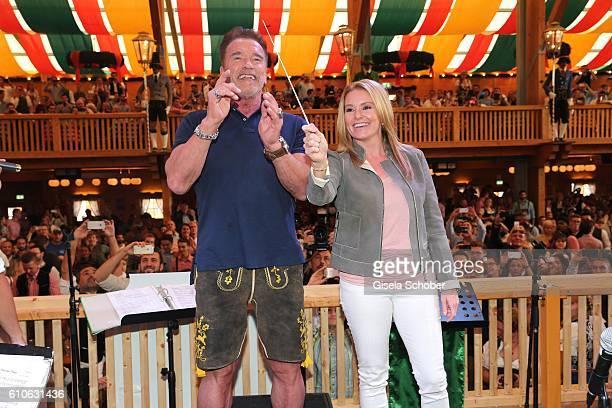 Arnold Schwarzenegger and his girlfriend Heather Milligan conduct the orchestra at the Schuetzen Festzelt during the Oktoberfest at Theresienwiese on...