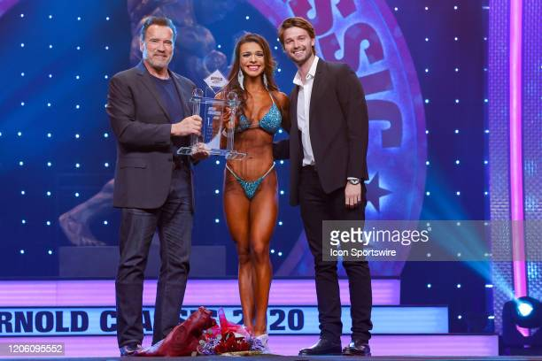 Arnold Schwarzenegger and Patrick Schwarzenegger present Alessia Facchin with the trophy for winning Bikini International as part of the Arnold...