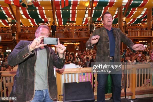 Arnold Schwarzenegger conducts the orchestra and Ralf Moeller photographs during the Oktoberfest at Schuetzen Festzelt at Theresienwiese on September...