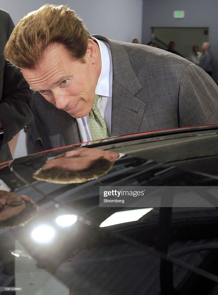 Arnold Schwarzenegger, governor of California, examines Tesla Motors Inc.'s Model S electric car at the company's headquarters in Palo Alto, California, U.S., on Thursday, May 20, 2010. Toyota Motor Corp. will acquire a $50 million stake in California electric-car maker Tesla Motors Inc. as automakers compete to introduce less-polluting vehicles in the U.S. Photographer: Tony Avelar/Bloomberg via Getty Images