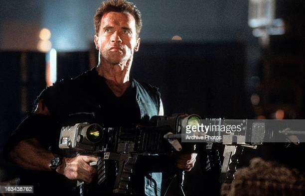 Arnold Schwarzenegger holding heavy weaponry in a scene from the film 'Eraser' 1996