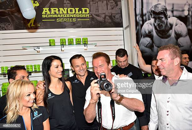 Arnold Schwarzenegger holds a camera as he poses with promotional staff at the Arnold Classic at The Melbourne Convention and Exhibition Centre on...