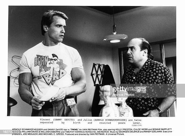 Arnold Schwarzenegger looking back at Danny DeVito in a scene from the film 'Twins' 1988