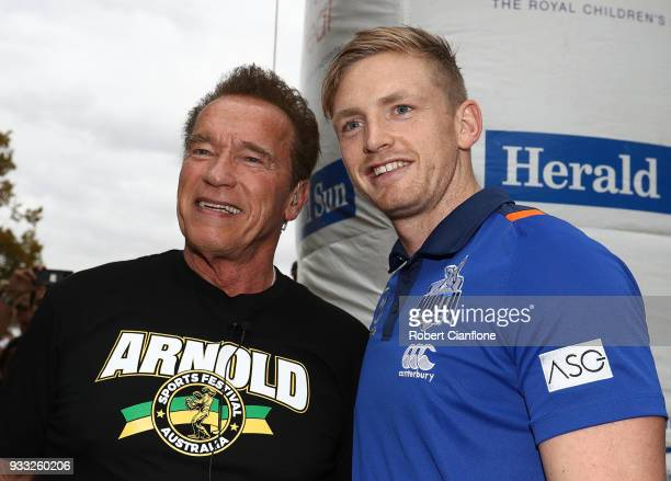 Arnold Schwarzenegger poses with Kangaroos AFL player Jack Ziebell as he prepares to start the Run for the Kids charity run as part of the Arnold...