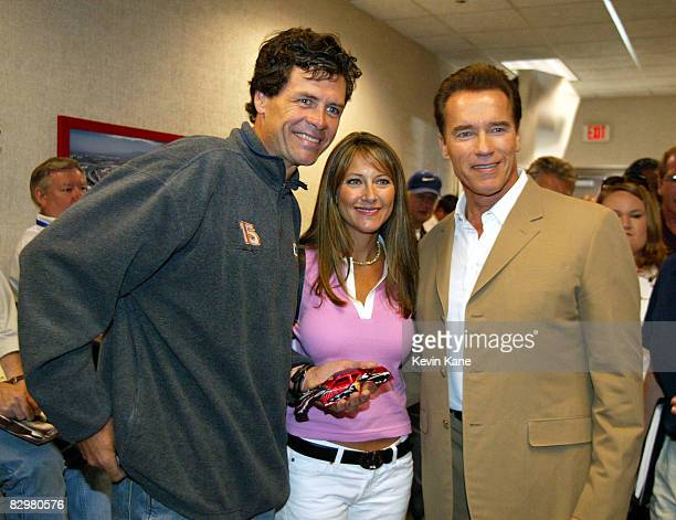 Arnold Schwarzenegger poses with Winston Cup driver Michael Waltrip and wife Buffy