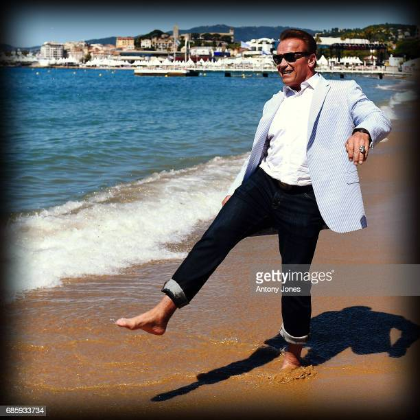 Arnold Schwarzenegger walks on the beach as he attends photocall for 'Wonders of the Sea 3D' during the 70th annual Cannes Film Festival at Nikki...