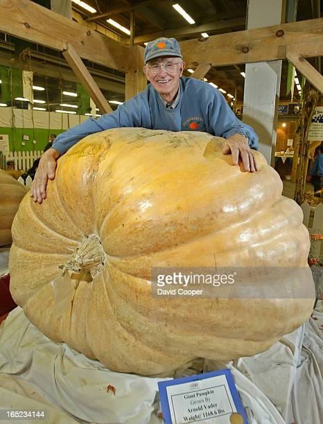 Arnold Vader of Prince Edward County hugs his prize winning 1168.6 lbs giant pumpkin during the last day at the 2003 Royal Winter Fair at the CNE...