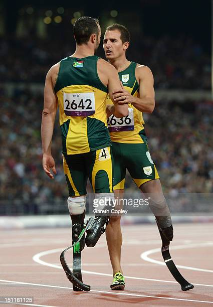 Arnu Fourie of South Africa speaks to Oscar Pistorius of South Africa after he finished with silver in the Men's 200m - T44 Final on day 4 of the...