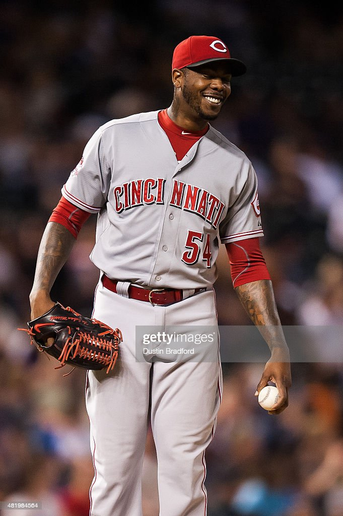 Aroldis Chapman #54 of the Cincinnati Reds smiles before coming into the game against the Colorado Rockies with two outs in the ninth inning inning of a game at Coors Field on July 25, 2015 in Denver, Colorado.