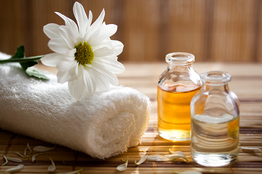 Aroma therapy oils placed next to a white towel and flower 174627639