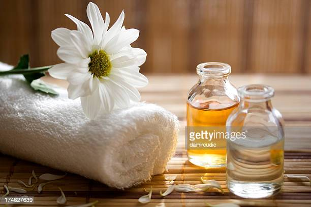 aroma therapy oils placed next to a white towel and flower - massage stock photos and pictures