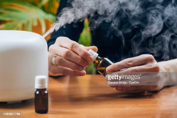aromatherapy essential oil home diffuser. adding natural aromatic essential oil into air humidifier - humidifier stock pictures, royalty-free photos & images